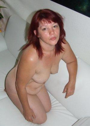 Пухлая рыжая женщина лежит голая на кровати